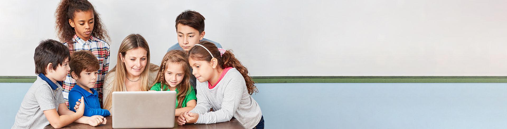 Groep kinderen met de juf achter de laptop